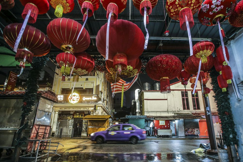 A taxi drives past a deserted Petaling Street duing the CMCO November 23, 2020. — Picture by Hari Anggara