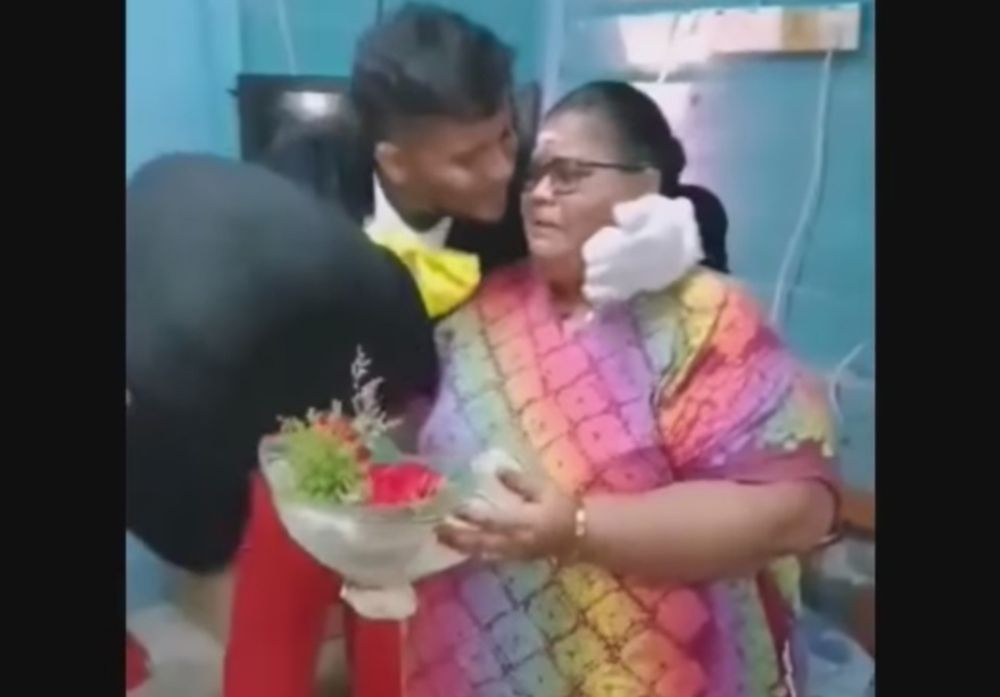R. Tanabalan giving his mother a peck on her cheek after removing his Mickey Mouse headpiece. — Screenshot from Facebook/ Rk Tana