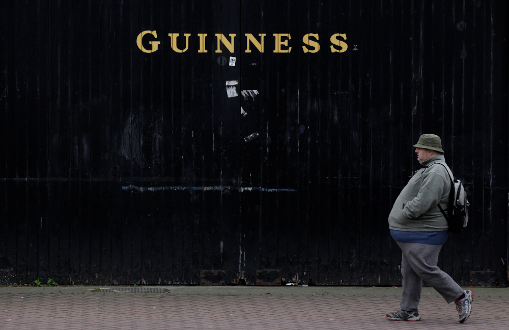 A man passes the Guinness beer factory in the city centre of Dublin December 6, 2011. — Reuters pic