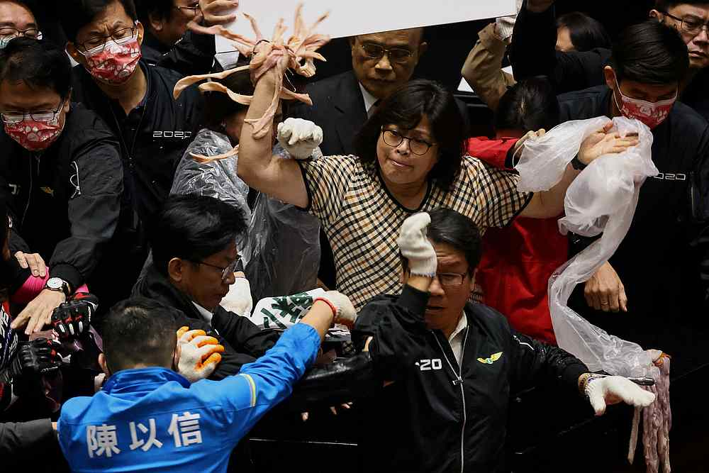 Taiwan lawmakers throw pork intestines at each other during a scuffle in the parliament in Taipei, Taiwan November 27, 2020. — Reuters pic