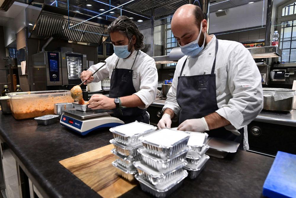 Michelin-starred Del Cambio restaurant, chef Matteo Baronetto (left) and his assistant Vittorio di Palma package a pasta dish with meat sauce. — AFP pic