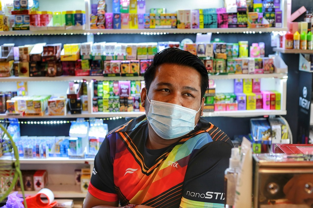Lokman Hakim bin Mohd Yusof, 25, runs Puppetborn Vape in Kampung Baru worries that his customers will return to smoking cigarettes.