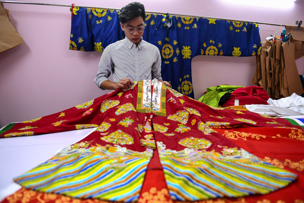 This photograph taken November 11, 2020 shows Nguyen Duc Loc, founder of the Y Van Hien company, checking an outfit based on traditional patterns and styles at his workshop in Hanoi. — AFP pic