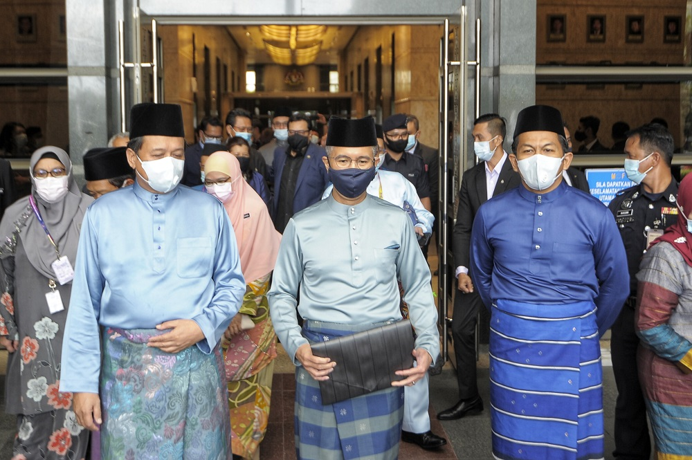 Datuk Seri Tengku Zafrul Abdul Aziz (second left) poses for cameras outside the Finance Ministry before leaving for Parliament to table Budget 2021 November 6, 2020. — Picture by Shafwan Zaidon
