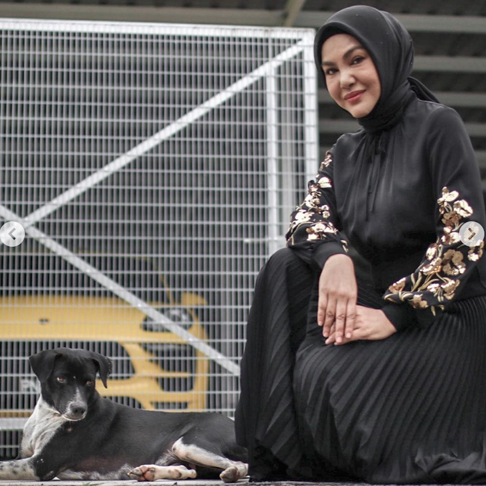 Umie Aida posing with Blackie, a female stray that she developed a close bond with since they crossed paths five years ago. — Picture from Instagram/myforeverdoggo