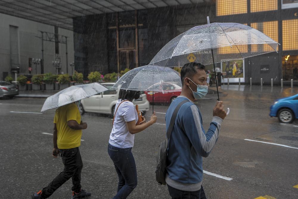 Pedestrians walking on the sidewalk while holding umbrellas in Bukit Bintang, Kuala Lumpur December 10, 2020. — Picture by Shafwan Zaidon