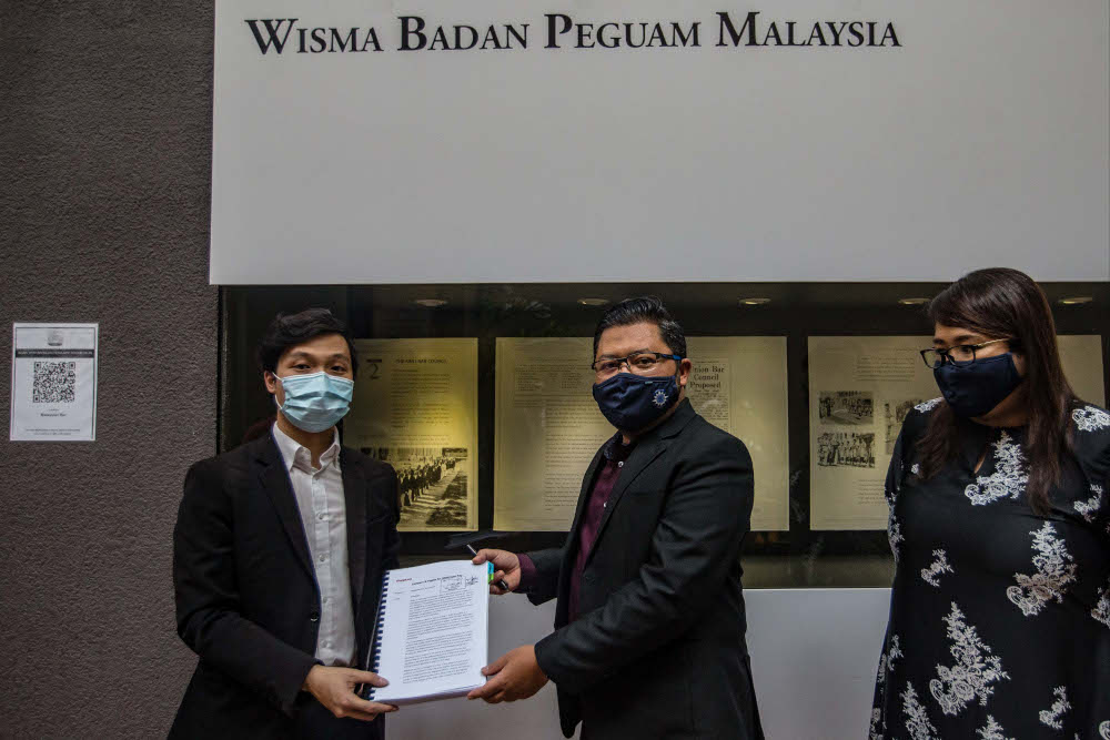 Lawyer Goh Cia Yee (left) handing the petition and signatures to National Young Lawyers and Pupils' Committee chairman Yusfarizal Yusoff (right), outside the Wisma Badan Peguam building in Kuala Lumpur December 16, 2020. — Picture by Firdaus Latif