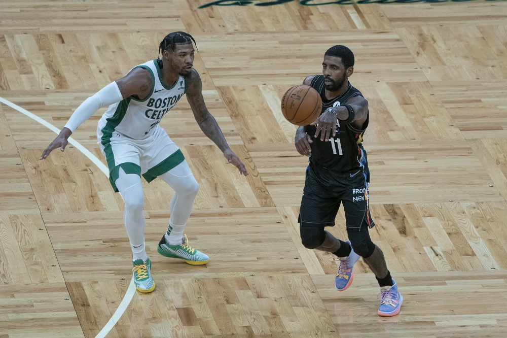 Brooklyn Nets point guard Kyrie Irving (11) passes the ball with Boston Celtics point guard Marcus Smart (36) defending during the third quarter at TD Garden in Boston December 26, 2020. ― Gregory Fisher-USA TODAY Sports via Reuters