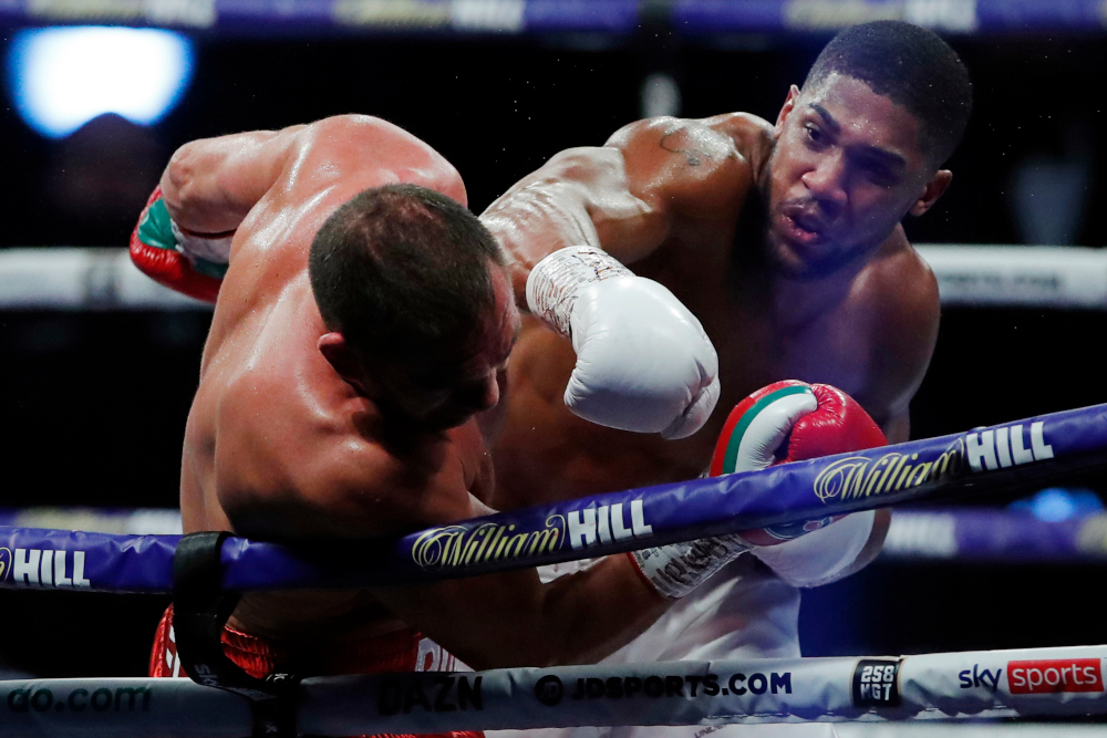 Britain's Anthony Joshua lands a punch on Bulgaria's Kubrat Pulev (left) during their heavyweight world title boxing match at Wembley Arena in north-west London December 12, 2020. — AFP pic