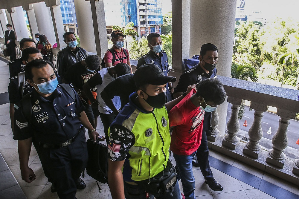 Four men who murdered ex-Mardi researcher Wan Hassan Wan Embong are seen at the Kuala Lumpur Court Complex December 9, 2020. — Picture by Hari Anggara