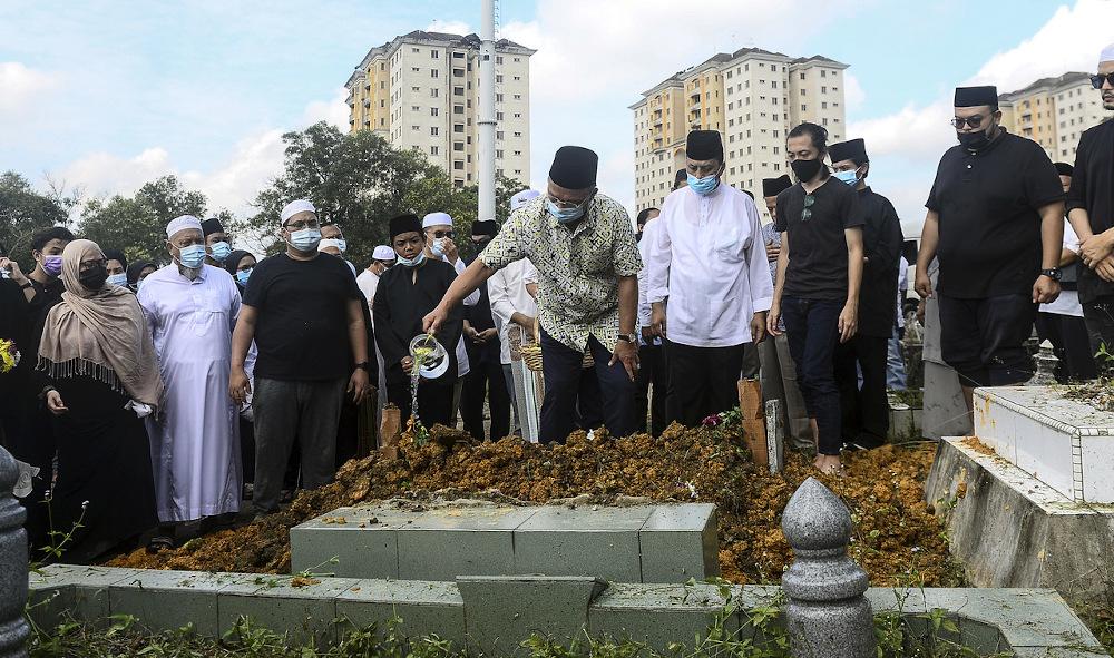 Johor Mentri Besar Datuk Hasni Mohammad sprinkles rose water on the grave of former Johor Speaker Tan Sri Mohamad Aziz in Johor Baru December 25, 2020. — Bernama pic
