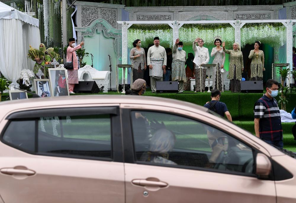 Datuk Seri Tengku Adnan Mansor (5th right), his wife Datin Seri Anggraini Sentiyaki (2nd right), the groom Tengku Muhammad Hafiz (centre) and bride Oceane Cyril Alogia (3rd right) wave to guests at Dataran Putrajaya December 20, 2020. — Bernama pic
