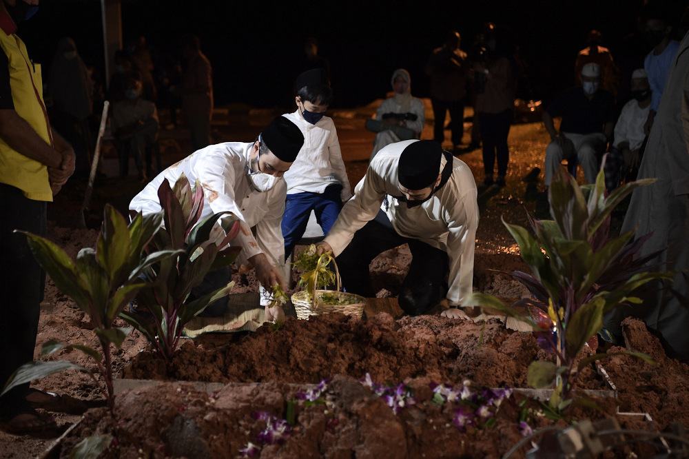 Family members scatter flowers at the grave of the late Royal Prof Ungku Abdul Aziz Abdul Hamid at the Bukit Kiara Muslim Cemetery December 15, 2020. — Bernama pic