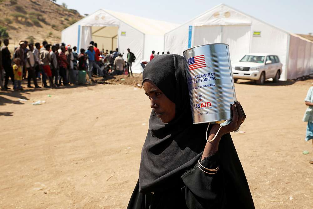 A woman carries a tin of food aid distributed by the WFP, at the Um Rakuba refugee camp which houses Ethiopians fleeing the fighting in the Tigray region, on the the border in Sudan, December 3, 2020. — Reuters pic
