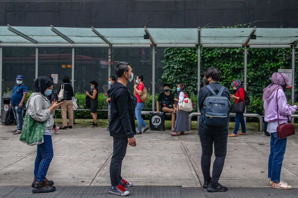 People wearing face masks observe social distancing while queuing at a bus stop in Kuala Lumpur December 18, 2020. — Picture by Firdaus Latif