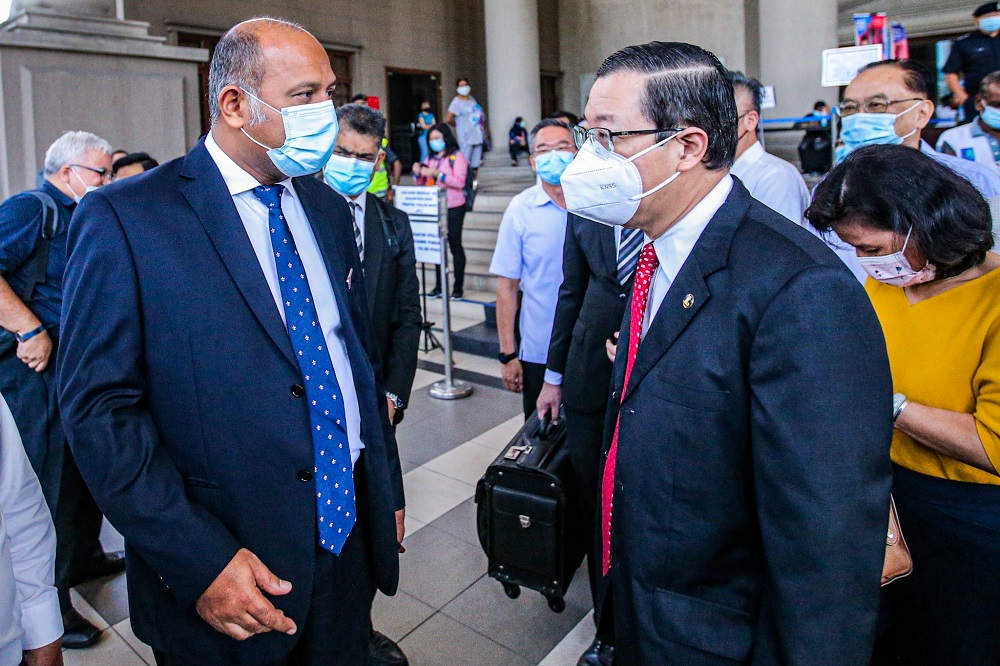 Lim Guan Eng (right) is seen with his lawyer Gobind Singh Deo outside the Kuala Lumpur High Court December 21, 2020. — Picture by Hari Anggara