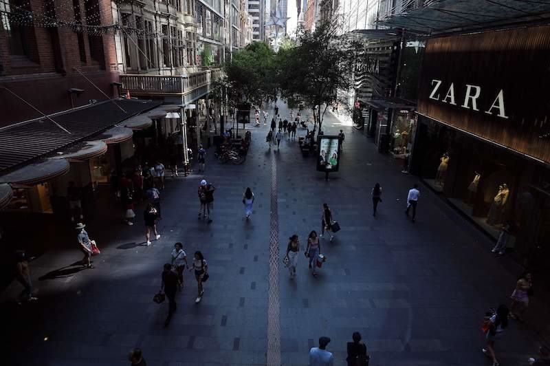 People walk through a downtown shopping arcade, usually packed with locals and tourists on Christmas Eve but now quiet due to Covid-19 concerns, in Sydney December 24, 2020. — AFP pic