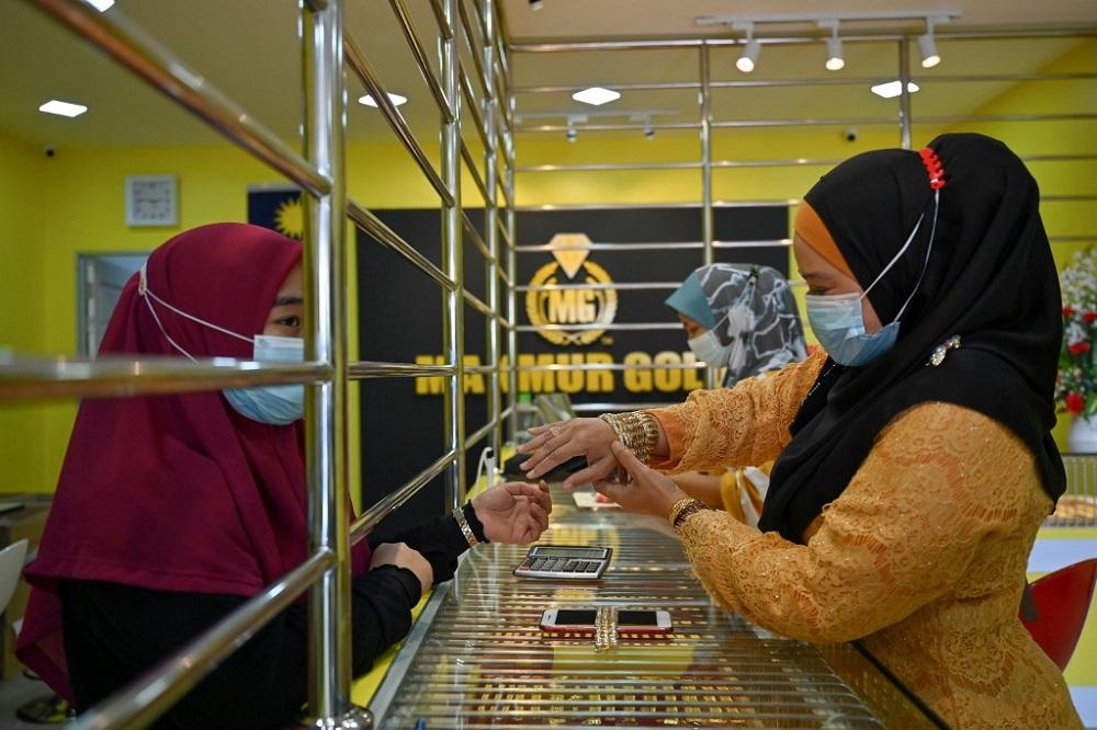 拍摄的这张照片显示了一位顾客正在尝试在2020年11月8日在哥打巴鲁的Makmur Gold商店里戴上手镯。―法新社图片