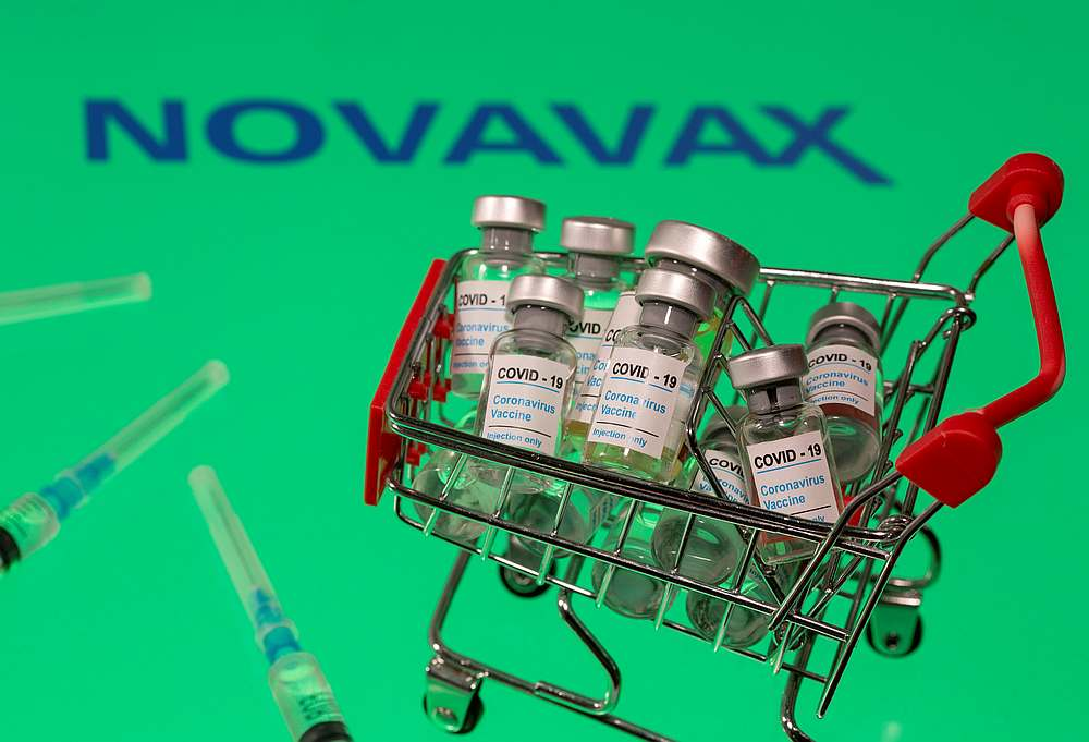 A small shopping basket filled with vials labelled 'Covid-19 — Coronavirus Vaccine' and medical sryinges are placed on a Novavax logo in this illustration taken November 29, 2020. — Reuters pic