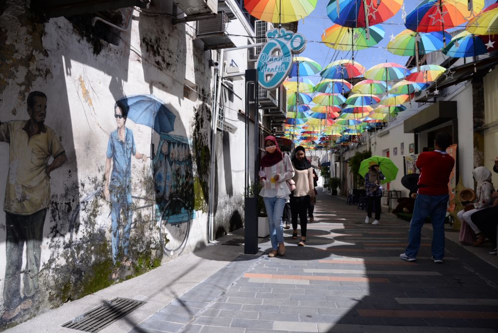 Visitors walk past street art at a heritage site in George Town December 22, 2020. — Picture by KE Ooi