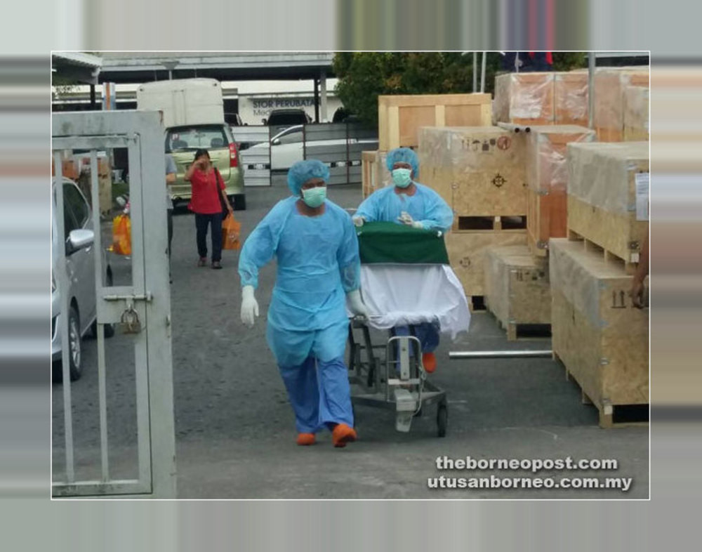 Medical personnel transporting the remains of a previous victim of rabies. The disease has claimed its 28th victim since the first outbreak in June 2017. — Borneo Post pic