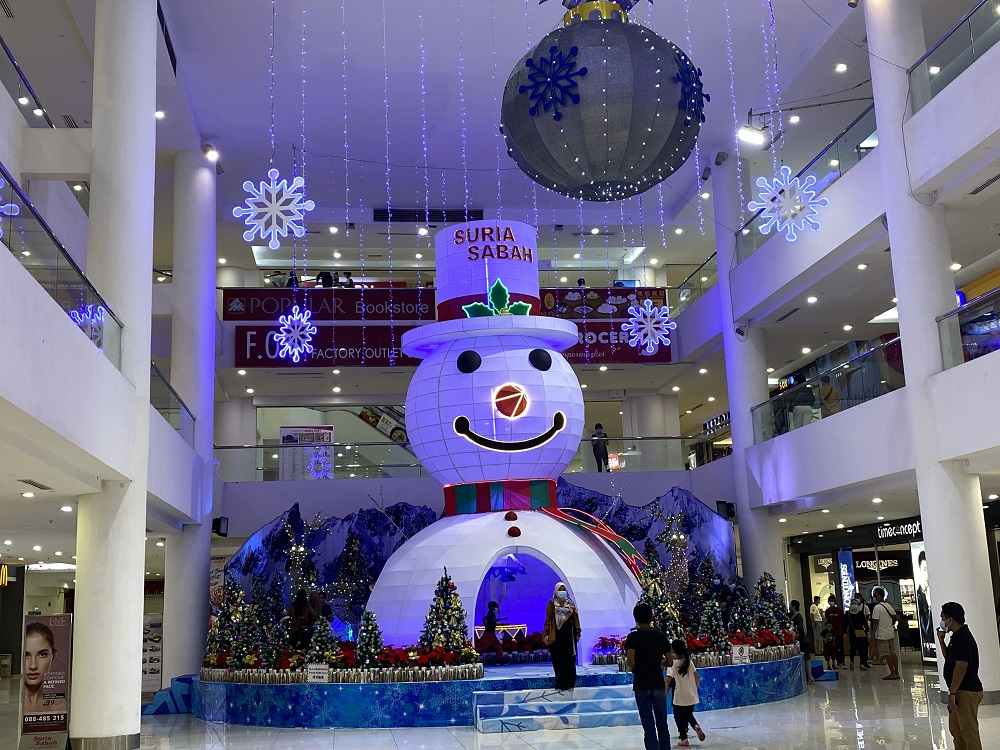 Visitors pose for a picture with the Christmas displays at a shopping mall in Kota Kinabalu. ― Picture by Julia Chan