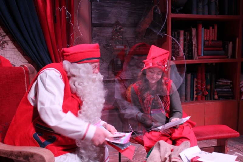Santa and his elf, Vanilla, read letters separated by a plexiglass screen in Rovaniemi at the Santa Claus Village amusement park, where visitor numbers have collapsed this year due to Covid-19. ― AFP pic