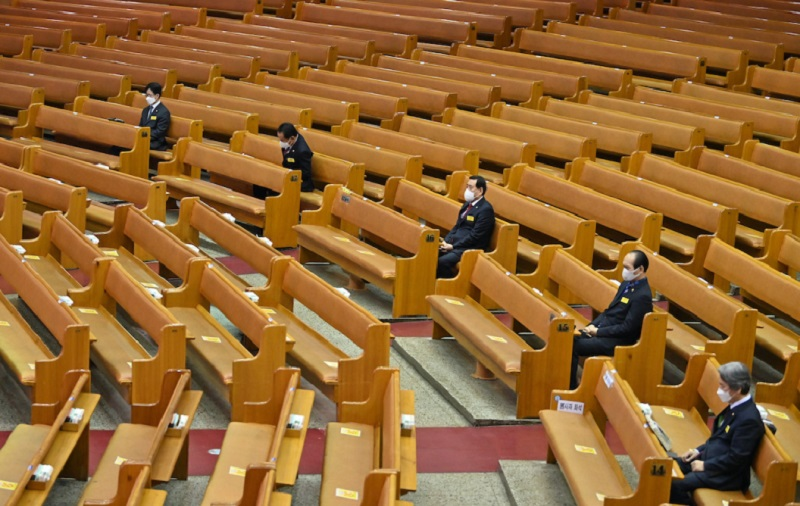 Pastors wearing face masks sit among empty benches during an online Christmas service at the Yoido Full Gospel Church in Seoul. ― AFP pic