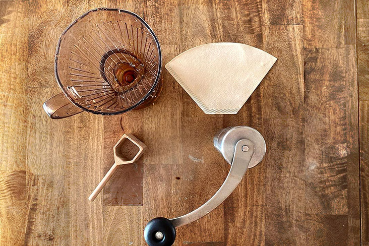 Coffee brewing paraphernalia: a Clever Dripper, a scoop, a grinder and unbleached filter paper.