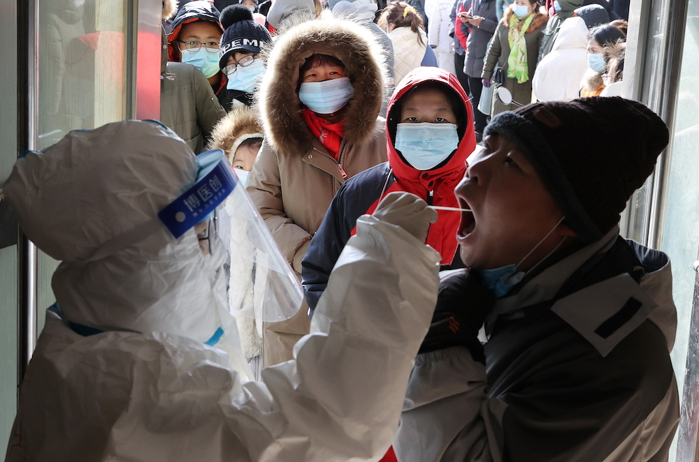 A medical worker in protective suit collects a swab from a resident during a mass nucleic acid testing following a recent Covid-19 outbreak in Shijiazhuang January 6, 2021. — China Daily via Reuters
