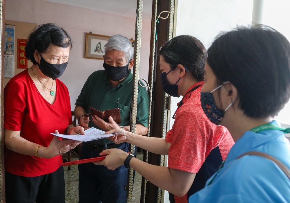 Volunteers doing house visits in Tanjong Pagar to inform senior residents on the national voluntary vaccination programme and to encourage them to get inoculated. — TODAY pic