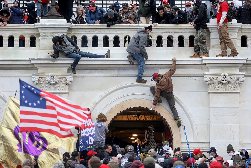A mob of supporters of US President Donald Trump fight with members of law enforcement at a door they broke open as they storm the US Capitol Building in Washington January 6, 2021. — Reuters pic
