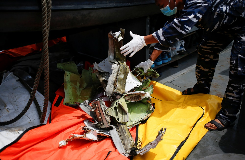 A member of the Indonesian navy inspects a piece of debris of Sriwijaya Air flight SJ182, which crashed to the sea, at the Jakarta coast January 12, 2021. — Reuters pic