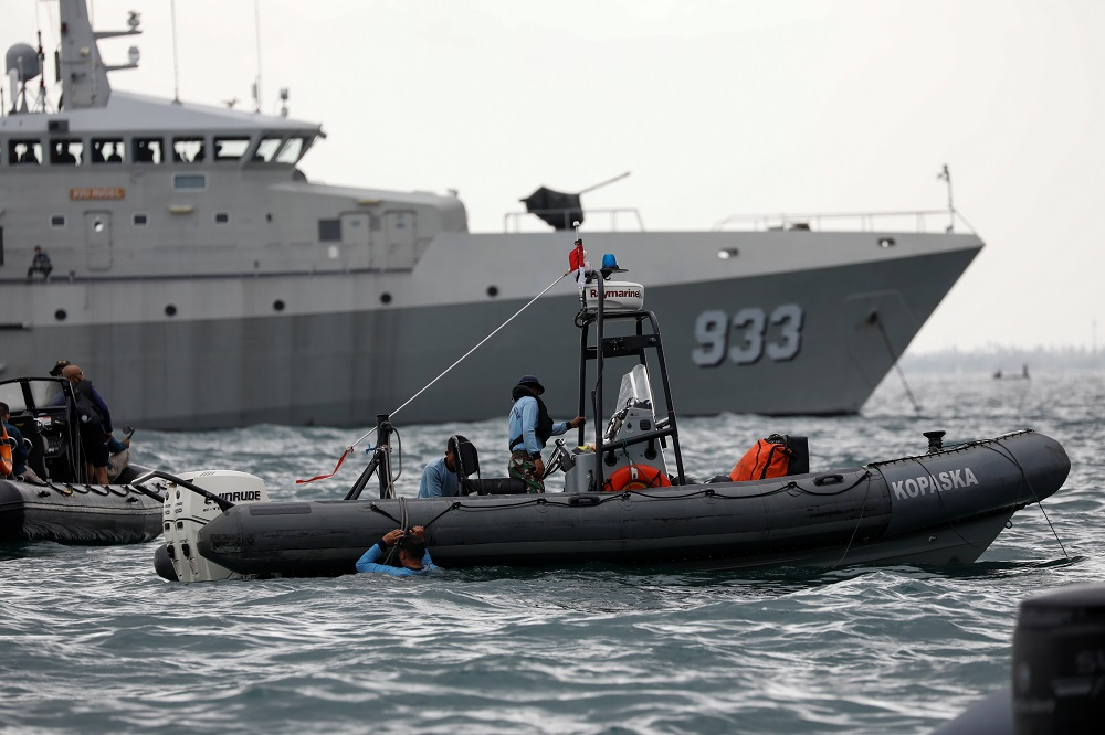 Indonesian navy divers stand on a rubber boat next to Indonesian naval warship KRI Rigel 933, during the search and rescue operation for the Sriwijaya Air flight SJ 182, at the sea off the Jakarta coast January 12, 2021. — Reuters pic