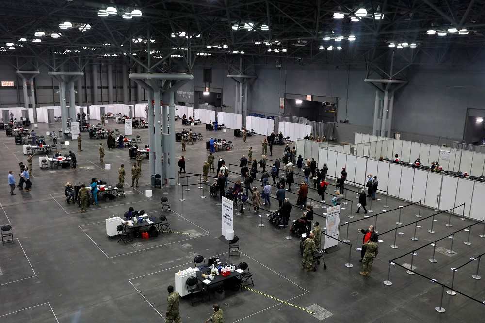 People line up as health care workers and military personnel work to distribute doses of the coronavirus disease vaccine at the New York State Covid-19 vaccination site at the Jacob K. Javits Convention Centre January 13, 2021. — Reuters pic