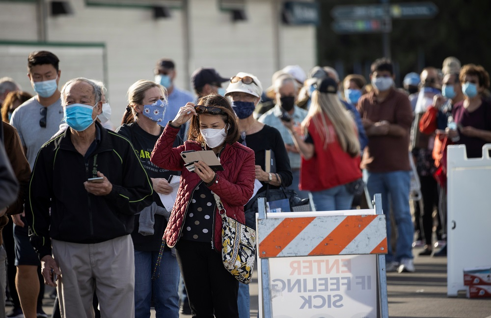 People wait in line in a Disneyland parking lot to receive a dose of the Moderna Covid-19 at a mass vaccination site in Anaheim January 13, 2021. — Reuters pic
