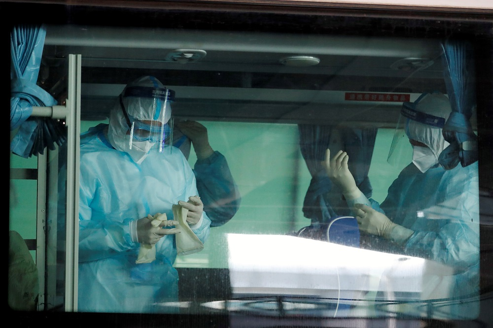 Medical workers get ready inside a bus before the expected arrival of a WHO team tasked with investigating the origins of the coronavirus disease pandemic, at Wuhan Tianhe International Airport in Wuhan, Hubei province, China January 14, 2021. — Reuters