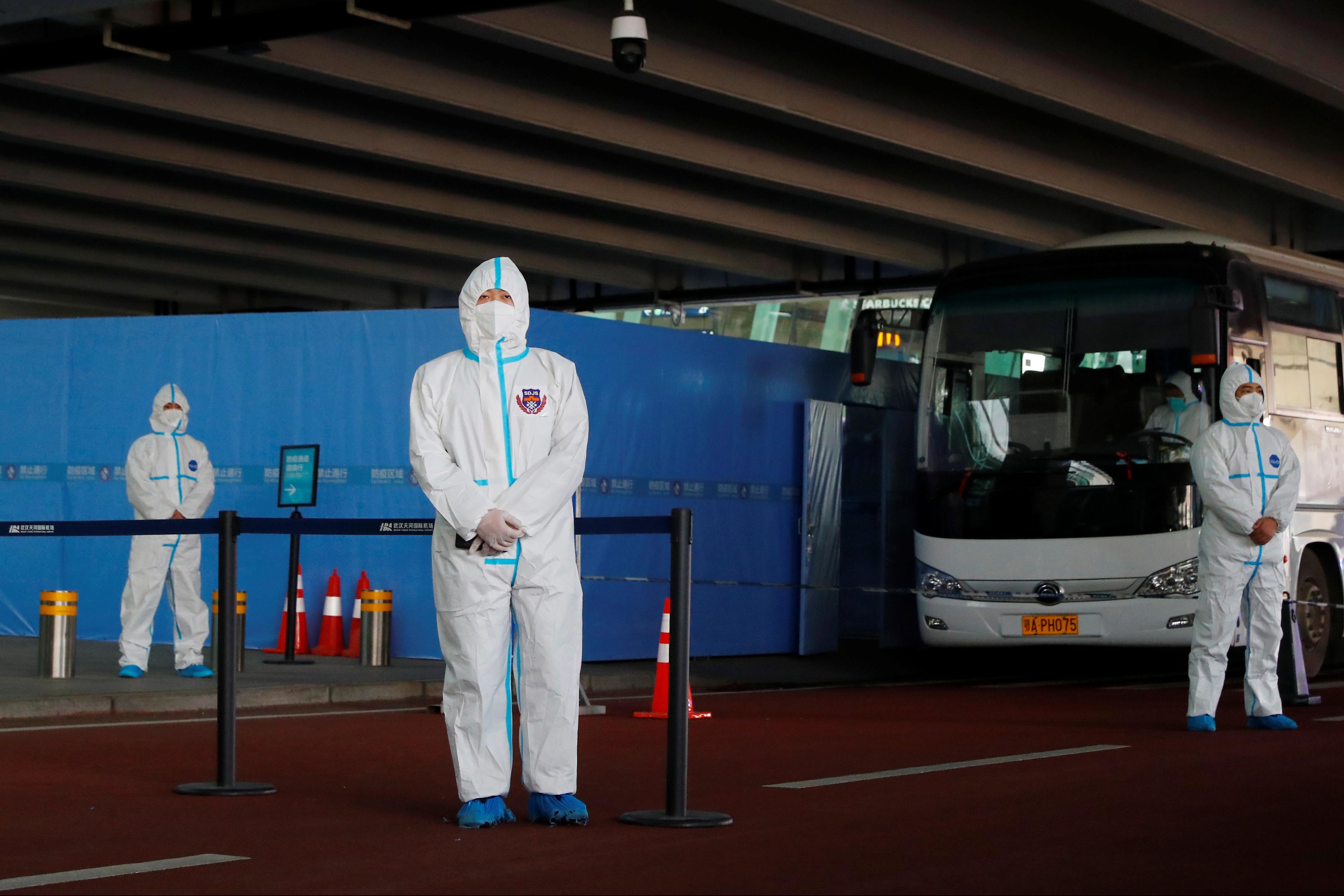 身穿防护服的工作人员在巴士旁守候,准备接载抵达武汉的世卫专家团。他们将先在当地接受隔离,之后才与中国专家展开调查工作。-路透社-