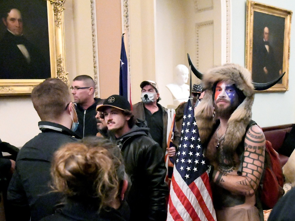 Jacob Anthony Chansley also known as Jake Angeli of Arizona stands with other supporters of US President Donald Trump as they demonstrate on the second floor of the US Capitol near the entrance to the Senate in Washingt