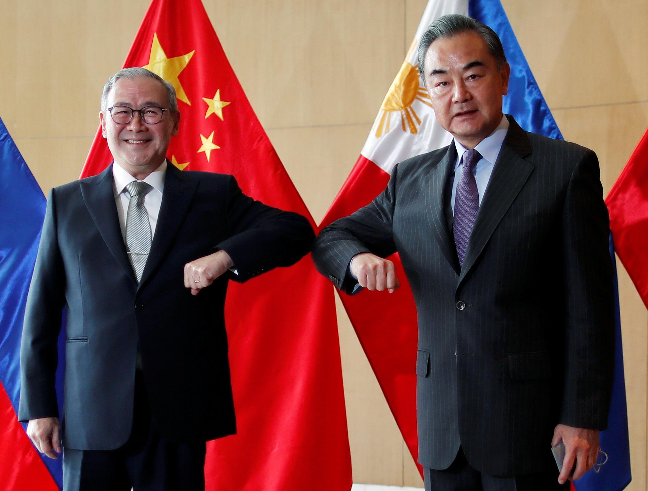 王毅(右)与菲律宾外长洛钦会谈,承诺捐赠50万剂新冠疫苗。-路透社-