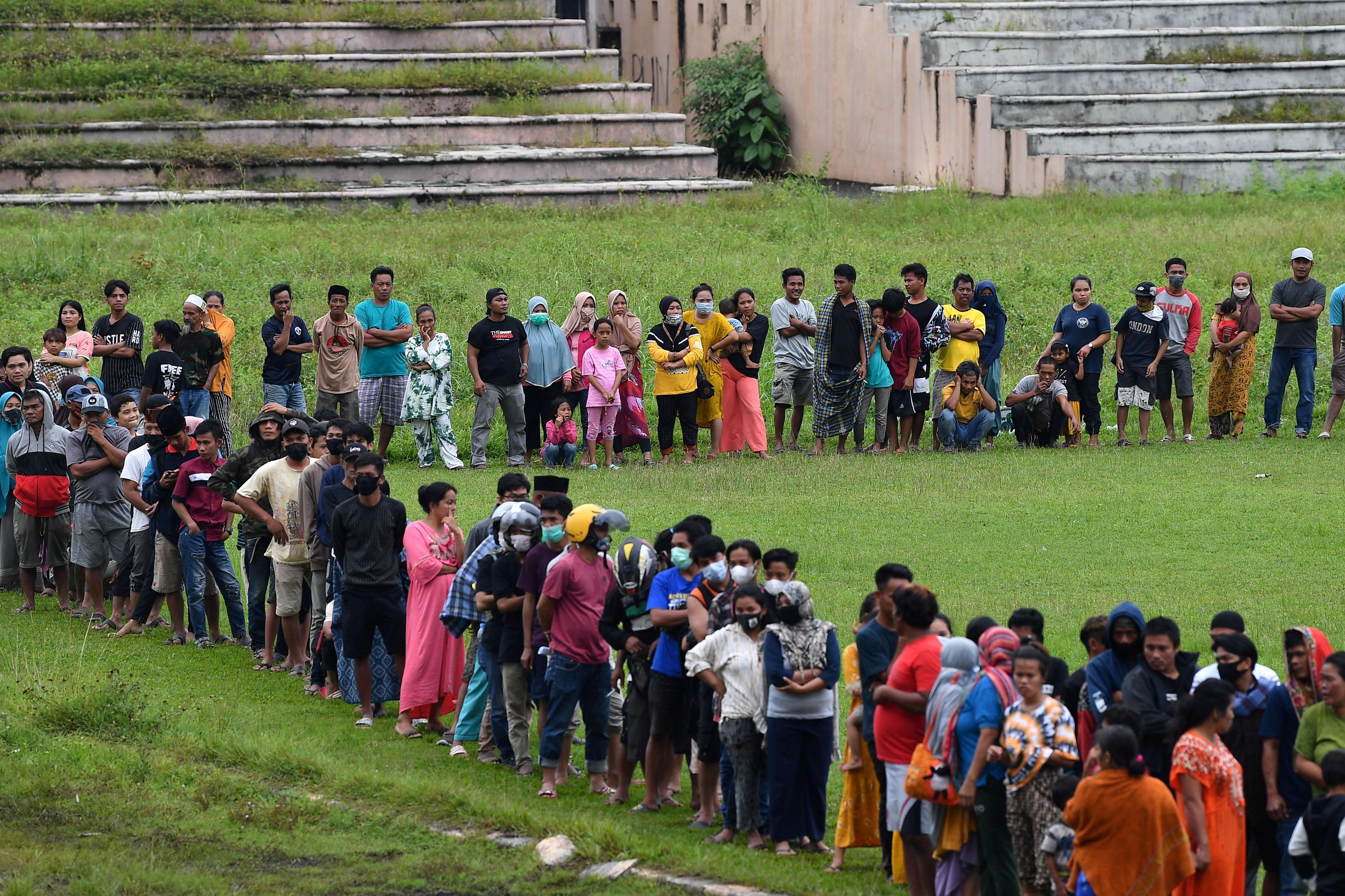 在强震中失去家园的民众,周日排队领取救援物资。他们目前只能挤进临时避难所。-路透社-