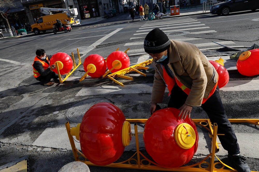 Workers wearing face masks assemble street lights in the shape of Chinese lanterns ahead of the Chinese Lunar New Year holiday, amidst the outbreak of the coronavirus disease, in Beijing January 26, 2021. — Reuters pic
