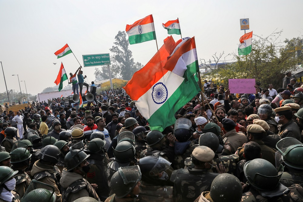 People shout anti-farmers slogans and wave India's flags as police officers try to stop them, at a site of the protest against farm laws at Singhu border near New Delhi January 29, 2021. — Reuters pic