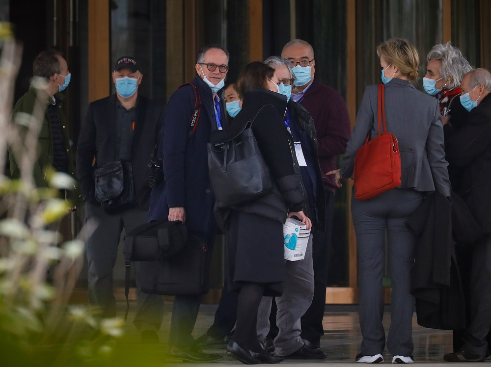 File photo of members of the World Health Organisation team tasked with investigating the origins of the coronavirus pandemic, talking outside their hotel after returning from their second field trip in Wuhan, Hubei province January 30, 2021. — Reuters pic