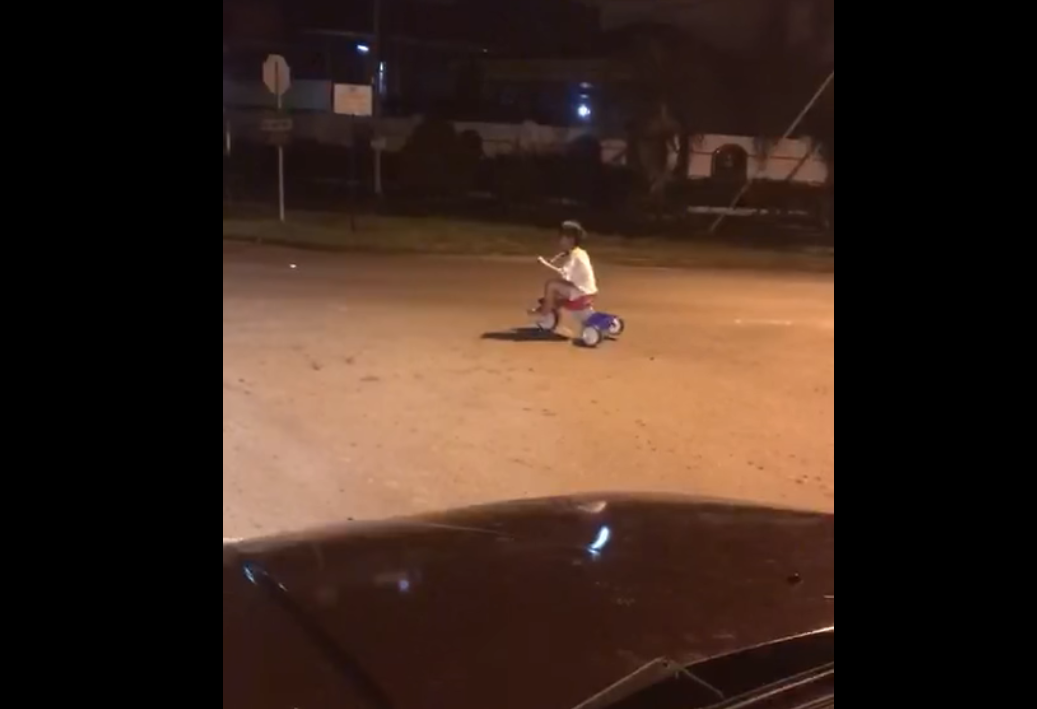 A little boy cycling alone in the middle of the night in a quiet neighbourhood spooks the villagers. — Screen capture via Facebook/myKKSabah