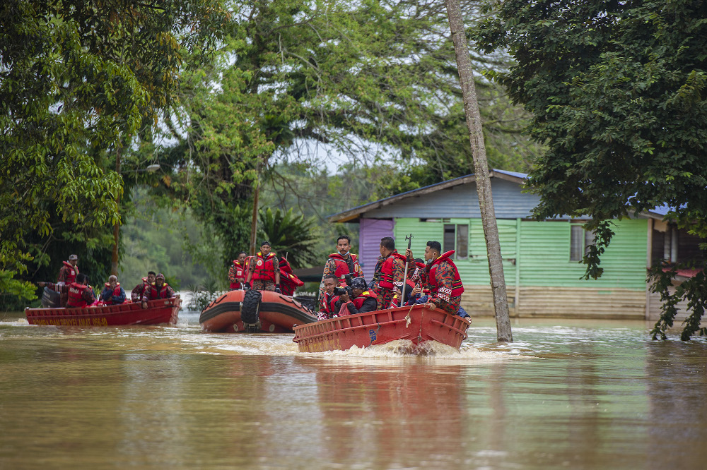 Search and rescue boat passes by submerged houses during flooding at Kampung Chenor, Maran in Pahang January 10, 2021. — Picture by Shafwan Zaidon