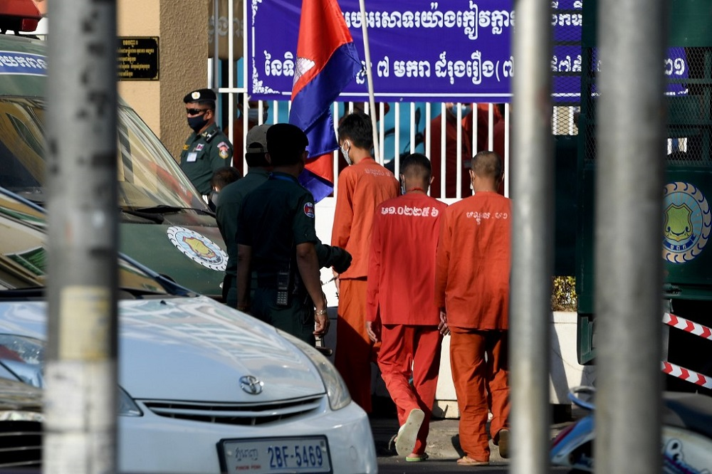 Jailed opposition members and activists walk from a prison van in front of Phnom Penh municipal court in Phnom Penh January 14, 2021. — AFP pic