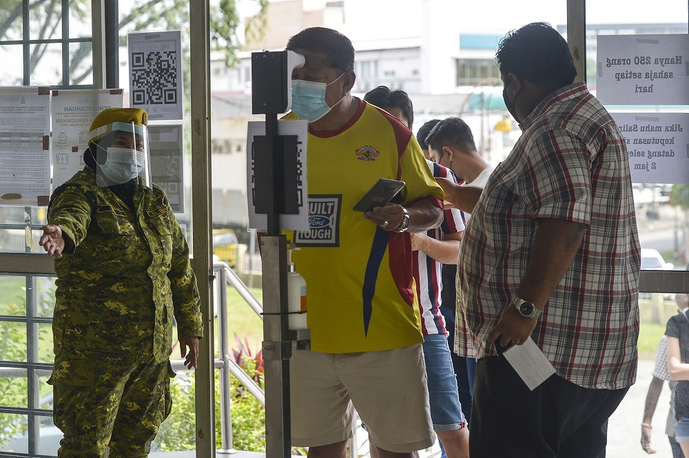Members of the public check their temperatures before entering a Covid-19 screening area in Petaling Jaya January 18, 2021. —  Picture by Miera Zulyana
