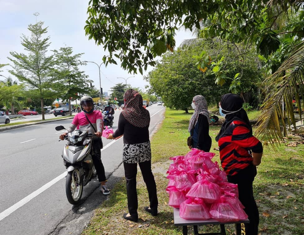 A Foodpanda delivery rider picking up food at the give out point at Jalan Cahaya in front of Taman Nirwana, Ampang on Wednesday. — Picture via Facebook/ Ida Azarin Razali