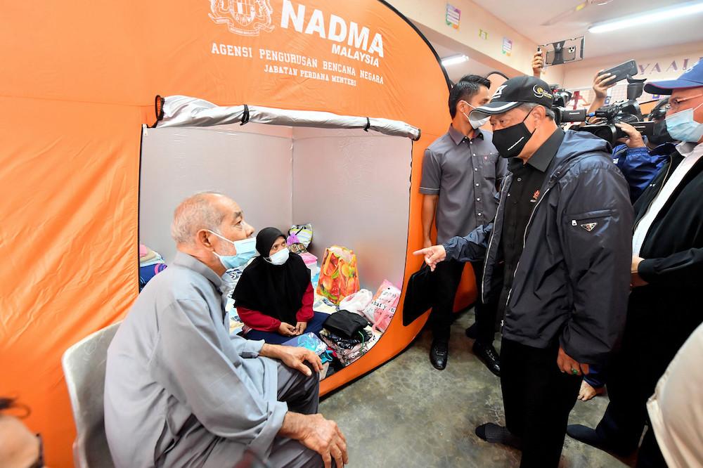 Prime Minister Tan Sri Muhyiddin Yassin mingling with flood victims during a visits at the temporary evacuation centre of Sekolah Menengah Kebangsaan (SMK) Seberang Temerloh Jan 10, 2021. — Bernama pic